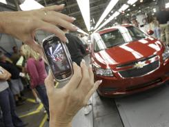 In this Sept. 8, 2010 photo, auto worker Brenda Hedland takes a picture of the first Chevrolet Cruze compact sedan to come off the assembly line.
