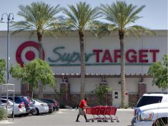 In this April 5, 2011 photo, a Target employee retrieves shopping carts outside a store in Gilbert, Ariz.