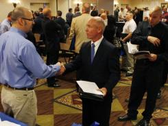 As a long line of job-seekers wait, Lockheed Martin military relations manager Dave Wallace, left, shakes hands with Joe Archatowski, of Lansdale, Pa., at a job fair aimed at helping military and former military members transition to civilian jobs, in Cherry Hill, N.J., on May 3, 2011.