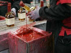 In this photo taken April 8, 2009, a bottle of Maker's Mark is dipped in the iconic red wax during a tour of the distillery in Loretto, Ky.