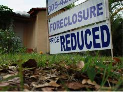 A foreclosure sign stands in front of a home for sale on Feb. 11. Foreclosures are taking weeks longer to complete than a year ago.