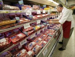 In this March 3, 2011 file photo, meat department manager Kevin Morlan arranges packages of pork at a local Dahl's grocery store in Des Moines, Iowa.