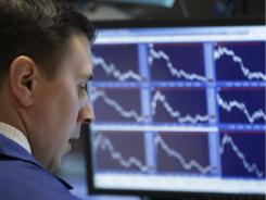 A specialist watches stocks fall from his booth on the floor of the New York Stock Exchange.