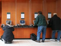 Customers at a TD Ameritrade office check online stock prices.