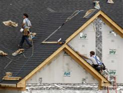 In this May 19, 2011 photo, roofers work on a new home  in  Bridgeville, Pa.