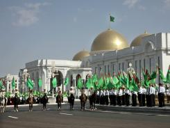 People hold national flags during opening ceremonies for a new presidential palace in Ashgabat, Turkmenistan, Wednesday, May 18, 2011.