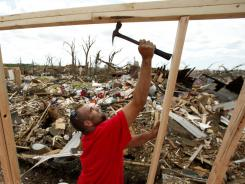 Phillip Law frames a wall as he helps rebuild a destroyed beauty salon in Joplin, Mo., on May 26.