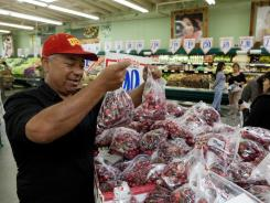 In this May 23, 2011 photo, customer Prieto Valenzuela shops for seasonal cherries at a Superior Grocers store in Los Angeles.