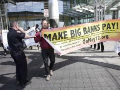 In this May 6, 2011 file photo, a police officer escorts protesters from a Goldman Sachs office building in Jersey City, N.J. after they attempted to enter the financial company's shareholders meeting.