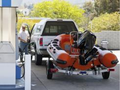 Travelers fill up at a gas station for an early start on the Memorial Day weekend traffic Friday in Valencia, Calif.