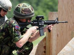 In this June 25, 2010, file photo Britain's Prince Harry fires a Colt M4 assault riffle on a United States Military Academy range in West Point, N.Y.