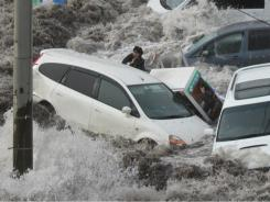 A newspaper reporter is swept up in tsunami waves March 11 in Kamaishi, in northeastern Japan. He survived.
