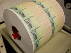 A roll of blank checks from the U.S. Treasury is readied for printing.