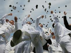 U.S. Naval Academy graduates throw their hats in the air during May 27 graduation ceremonies.