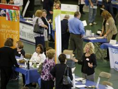 In this May 25, 2011 photo, people meet with perspective employers at the Jobapalooza job fair at Lake Erie College, in Painesville, Ohio.