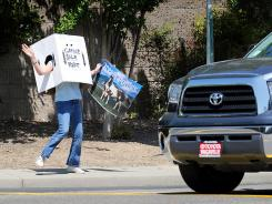 In this April 25, 2010 file photo, Jessica Dorough, 14, earning a $5 salary and dressed in her standard issue garage sale robot uniform, beckons customers to a  family sale in south Vacaville, Calif.