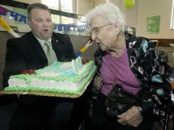 June Gregg, right, of Bainbridge, Ohio, blows out the candles on her birthday cake held by Doug Shoemaker, community president and branch general manager of the Chillicothe branch of Huntington National Bank, to celebrate Gregg's 100th birthday at the bank June 2, 2011 in Chillicothe, Ohio.