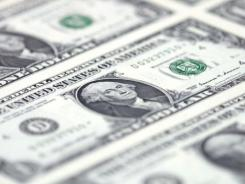Freshly printed dollar bills await cutting and bundling at the Bureau of Printing and Engraving.