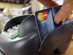 A customer swipes a debit card while checking out at a shop in Seattle in this file photo.
