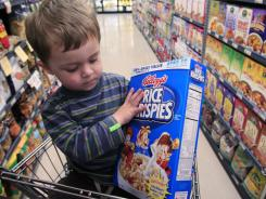 Evan Olmstead, 2, looks at cereal at Piazza's grocery store in Palo Alto, Calif. Higher food and energy prices could actually keep other prices from rising.