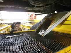 An employee changes oil at a Jiffy Lube in Sylmar, Calif.