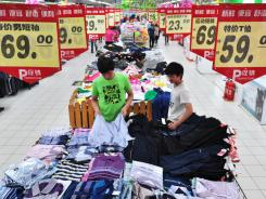 Chinese customers select items on sales at a supermarket in Binzhou, east China's Shandong province on June14, 2011.