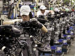 Employees assemble VQ engines June 14 at a Nissan plant in Iwaki, Japan.