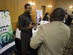 In this July 20, 2010 photo, Cedric James, left, admissions director with MyComputerCareer.Com,meets with a prospective job applicant at a National Career Fairs Job Fair in Plano, Texas.