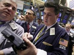 Traders work on floor Monday of the New York Stock Exchange.