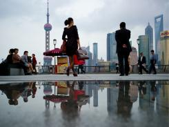 Pedestrians walk past the Shanghai financial district in China, October 8, 2010.