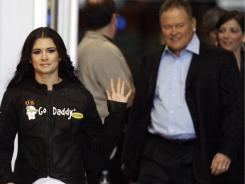 driver Danica Patrick, left, waves to the crowd as she is joined by Go Daddy CEO and founder Bob Parsons, middle, and Kelley Earnhardt, far right, vice president and general manager of JR Motorsports, before unveiling her GoDaddy.com No. 7 JR Motorsports stock car during an event on Dec. 8, 2009, in Phoenix, Arizona.