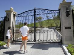 Joggers look at the front gate of a hidden $100 million mansion in Los Altos Hills, Calif.