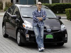 Warren Hu poses with his new Toyota Prius in Redwood City, Calif. in March. The EPA already rates Prius 50 mpg in combined city/highway driving.
