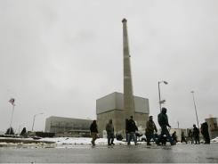 In this Thursday, Feb. 25, 2010 picture, workers walk in front of a large square structure that houses the nuclear reactor at the Oyster Creek nuclear plant in Lacey Township, N.J. This boiling water reactor began running in 1969 and ranks as the country's oldest operating commercial nuclear power plant.
