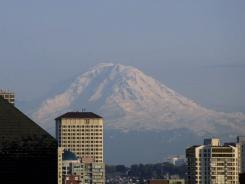 Mt. Rainier, a 14,411-foot volcano,  is seen between downtown Seattle buildings just before sunset Sunday, May 7, 2000.