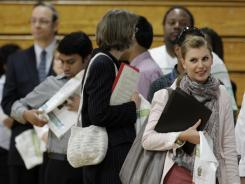 In this June 15, 2011 photo, job seekers stand in line at a job fair in Southfield, Mich.