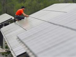 A man works on solar panels in Burlington Township, N.J.