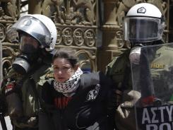 Riot police detain a protester during clashes in Athens, Wednesday, May 11, 2011.