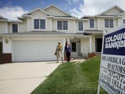 Realtor Kathi Dellaca and Kim Hiscox, of West Des Moines, right, walk out of a home for sale recently in Urbandale, Iowa.