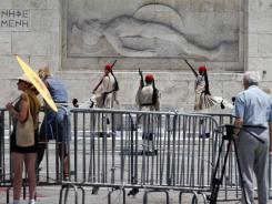 Tourists watch the change of the guard at the Tomb of the Unknown Soldier behind a police barricade blocking access  in central Athens Thursday, June 30, 2011.