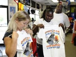 Brenda Mulberry, left, owner of  Space Shirts, helps Cassandra Keith and Darrell Farmer with a custom design.