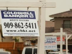 For sale signs line a residential street in Adelanto, Calif., in June 2009.