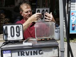 Convenience store owner Floyd Bisson lowers the price of regular gas at the pumps in front of his store in Phippsburg, Maine on  Monday, June 27, 2011.