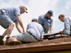 Phelps Heating and Cooling employees install solar panels on a roof in Hardin County, Ky., on June 23.