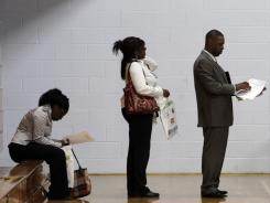 In this June 15, 2011 photo, job seekers wait in a line at a job fair in Southfield, Mich.