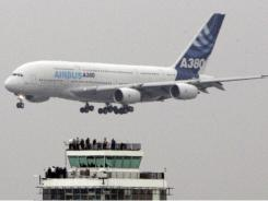 An Airbus A380, the world's largest passenger jet, passes the old control tower at Los Angeles International Airport.