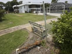 An empty park bench and rusting pipe sit near the swimming pool at the Inlet House, in Fort Pierce, Fla., June 15, 2011.