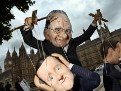 A demonstrator dressed in a Rupert Murdoch mask controls puppets of British leaders at a protest Friday.