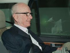 News Corp. chief Rupert Murdoch leaves his London home in a car with a copy of the Wall Street Journal newspaper beside him on July 13, 2011.