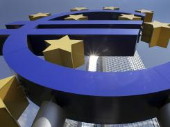 The sun is reflected on the facade of the European Central Bank ECB Tower, seen through the Euro symbol,  in Frankfurt, central Germany.